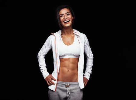 mujer deportista: Sonriendo deportista en ropa deportiva en el fondo negro. Modelo de fitness caucásico que mira feliz con las manos en las caderas.