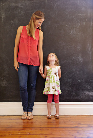 full: Full length shot of sweet little girl standing with her mother at home. Mother and daughter looking at each other against a wall, indoors.