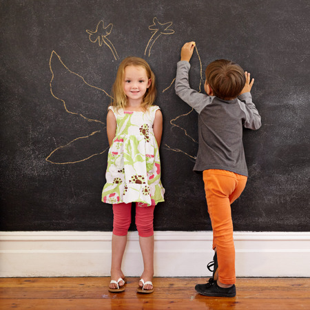 Full length portrait of cute little girl standing and little boy drawing angel wings around her on blackboard. Фото со стока