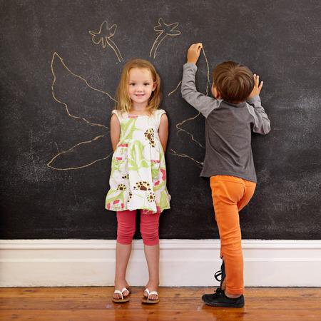 Full length portrait of cute little girl standing and little boy drawing angel wings around her on blackboard. Standard-Bild