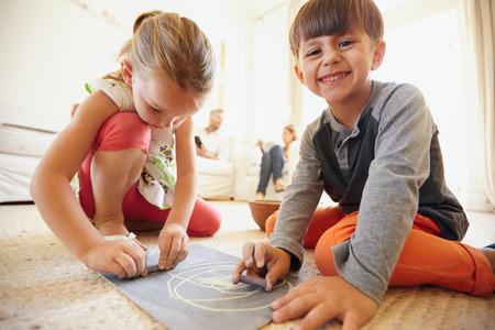 niños sentados: Tiro de interior de los pequeños niños felices dibujar y colorear sentado en el piso con los padres en el fondo como en casa