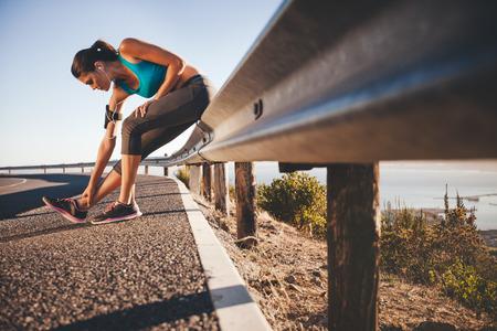 スポーツ女性の屋外を実行した後彼女の足を伸ばします。女性アスリートは、高速道路のガードレールに座ってトレーニングを実行した後休憩しま