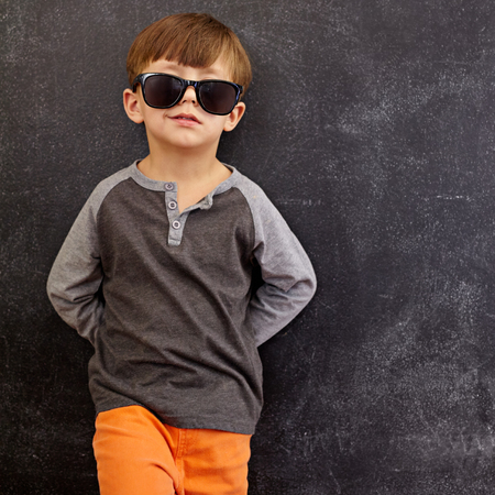 cute boys: Portrait of smart little boy wearing sunglasses smirking. Cool kid in shades leaning on a blackboard looking at camera smiling with copy space.