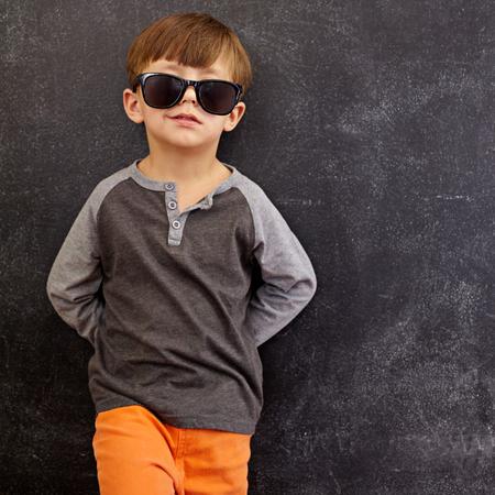 Portret van slimme kleine jongen draagt een zonnebril grijnzende. Cool kid in de kleuren leunend op een schoolbord te kijken naar de camera lacht met kopie ruimte.