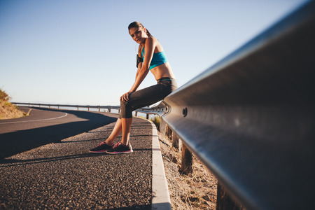 guardrail: Tired young woman relaxing after a outdoor training session. Runner resting on road guardrail after morning run. Stock Photo