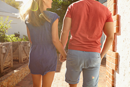 causal: Rear view shot of a young couple holding hands taking a walk outside in their backyard. Cropped shot of young couple outdoors on a bright sunny day. Stock Photo