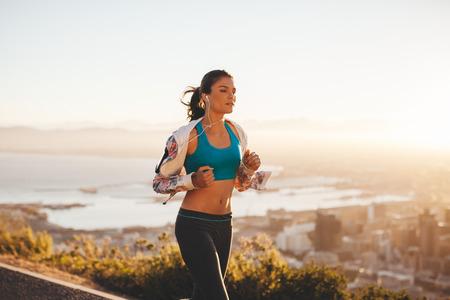 atleta: Mujer joven apta para correr al aire libre. Atleta femenina en la carrera por la mañana con la luz brillante.
