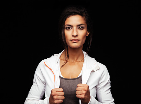 woman black background: Shot of young fitness model posing in studio. Healthy young woman in sportswear standing against black background. Stock Photo