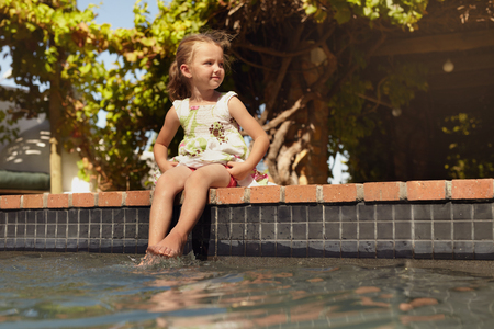 only one girl: Outdoor shot of a little girl dipping her feet in the pool looking away. Cute little girl sitting on the edge of a swimming pool on a sunny day. Stock Photo