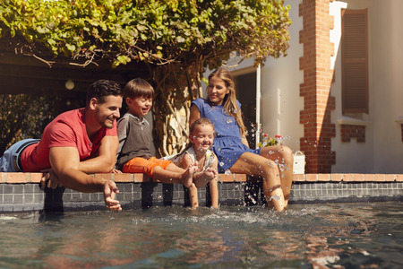 family playing: Outdoor shot of happy young family splashing water with hands and legs while sitting on edge of swimming pool. Family enjoying a hot sunny day playing by the pool.