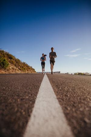 actividad fisica: El ángulo inferior tiró de dos jóvenes que se ejecutan en la carretera. Correr en la carretera nacional en un día de verano. Foto de archivo