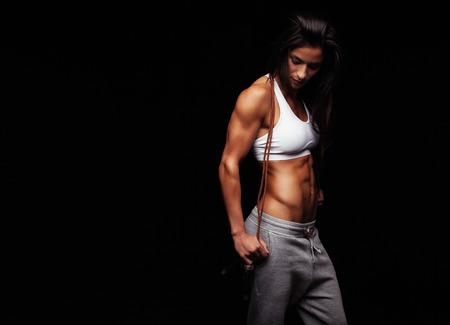 saltar la cuerda: Tirado de mujer joven ejercicios con una cuerda para saltar mirando hacia abajo. Mujer muscular con saltar la cuerda contra el fondo negro, copyspace. Foto de archivo