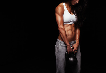pesas: Recortar foto de la mujer atleta que hace ejercicio de la construcción del cuerpo con la campana hervidor de agua sobre fondo negro.
