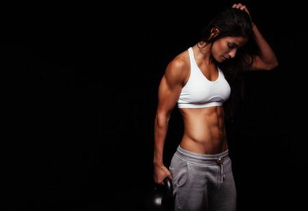 fortaleza: Fitness mujer ejercicio crossfit campana celebración hervidor de agua. Instructor de la aptitud en el fondo negro. Modelo femenino con ajuste muscular y cuerpo delgado.