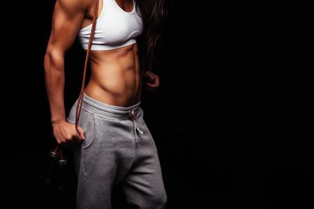 deportistas: Close up de torso de mujer joven. Músculos del abdomen perfecto de un atleta femenina que sostiene saltar cuerdas sobre fondo negro con copyspace.