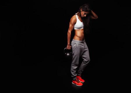 fitness: Mulher da aptidão que faz o exercício com crossfit chaleira sino. Instrutor da aptidão no fundo preto. Modelo fêmea com corpo musculoso, em forma e magro.