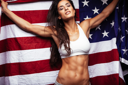 Sporty young woman holding American flag. Fitness female with perfect abs. Stock Photo