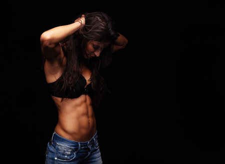 nude female body model: Muscular young woman standing against black background with her hands in hair looking down. Female model wearing bra and jeans.