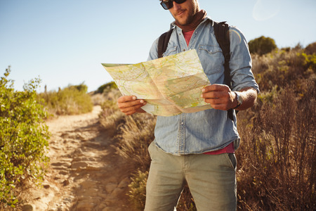 one young man: Shot of a man in countryside with a map, figuring out his orientation. Male hiker hiking in country.