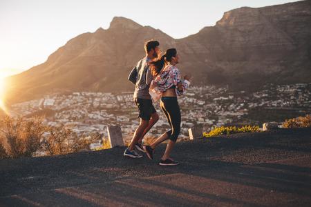 若い男と女の丘の中腹の道をジョギングのショット。自然の中を実行している若いカップル。