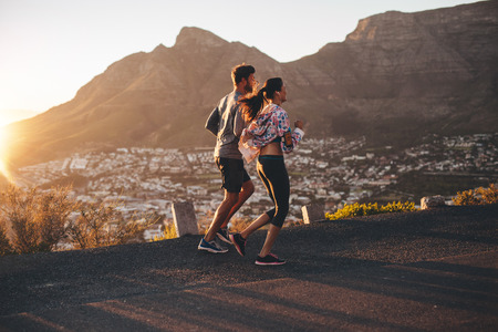 men running: Shot of young man and woman jogging on hillside road. Young couple running in nature. Stock Photo