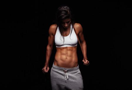 musculoso: Retrato de mujer muscular que sostiene la cuerda de salto. Modelo femenino de fitness con saltar la cuerda en el fondo negro