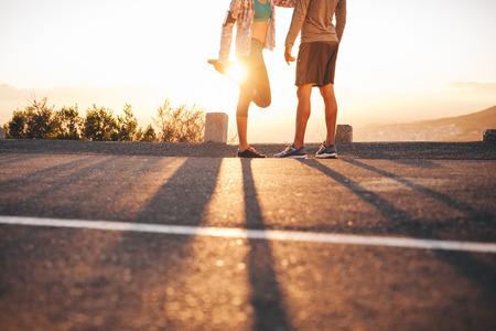 Bijgesneden shot van fit jonge paar warming-up voor een run samen bij zonsopgang. Jonge man en vrouw te oefenen in de ochtend.