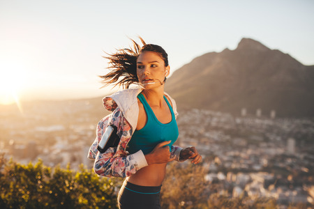 Female runner running outdoor in nature. Young woman jogging in morning looking over shoulder. Stock Photo