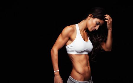검은 배경에 서있는 동안 스포츠에서 젊은 여자의 이미지는 생각을 착용하십시오. 사려 깊은 피트니스 모델. 스톡 콘텐츠