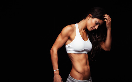 bra model: Image of young woman in sports wear thinking while standing against black background. Thoughtful fitness model. Stock Photo