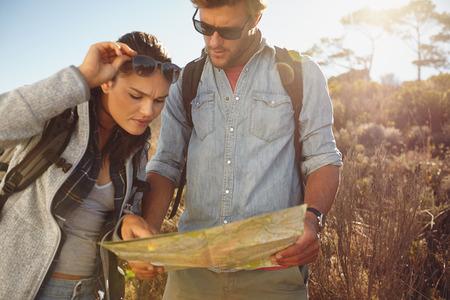 地図を見てハイカー。カップル旅行の間に一緒に移動するハイキング屋外の田舎。