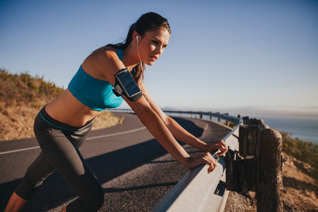 female body: Young female athlete leaning on highway guardrail looking away. Woman runner outdoors on country road taking a break after running exercise.