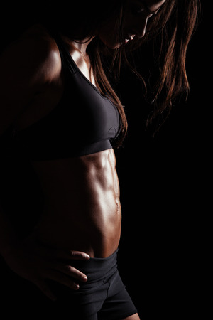 background black: Cropped image of muscular young woman posing in sportswear. Fit female model with perfect torso in studio. Stock Photo