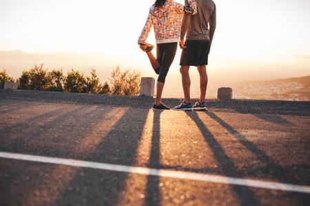 estiramientos: Recortar foto de hombre y mujer de pie en la carretera de la ladera en la mañana. Mujer que estira su pierna. Un par de corredores que buscan en la salida del sol.