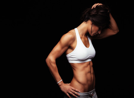 bra model: Image of fit young woman in sports wear looking down while standing on black background. Muscular fitness model wearing sports bra. Muscular abs. Stock Photo