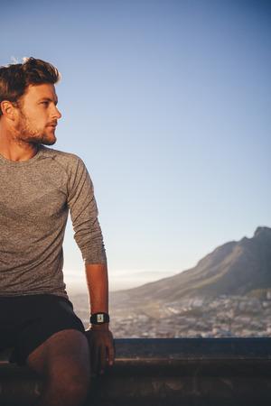 hombre deportista: atleta masculino de la aptitud al aire libre de descanso después de la formación. Joven se relaja después de correr por la mañana que mira lejos el espacio de la copia. Foto de archivo