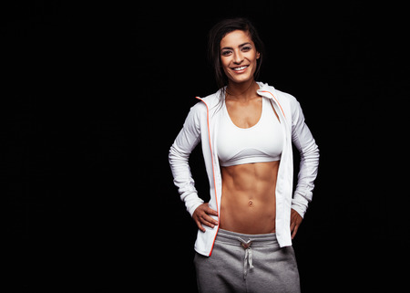 Confident athletic woman with muscular abs posing in sports clothing. Happy young female model in sportswear standing with her hands on hips against black background.