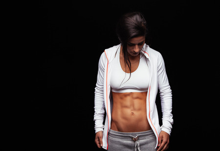 Portrait of a fit young woman with perfect abdomen muscles in sportswear. Muscular female athlete looking down on black background with copy space.