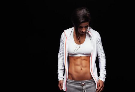 deportista: Retrato de una mujer joven del ajuste con los m�sculos del abdomen perfecto en la ropa deportiva. atleta femenina muscular que mira hacia abajo sobre fondo negro con copia espacio.