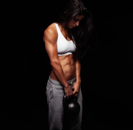 mujeres fitness: Mujer joven el ejercicio crossfit con el peso de campana hervidor de agua. crossfit femenina que se resuelve en fondo negro.