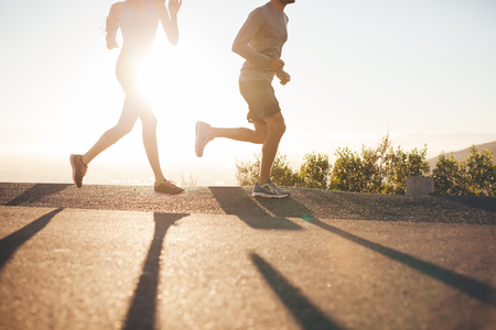 Low angle view of two people running on country road at sunrise. Cropped shot of young man and woman jogging in morning, with bright sunlight.