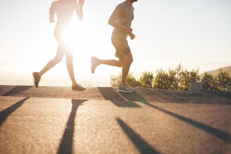 hacer footing: Ángulo de visión baja de dos personas que se ejecutan en la carretera nacional en la salida del sol. Recortar foto de hombre joven y una mujer corriendo en la mañana, con la luz del sol brillante.