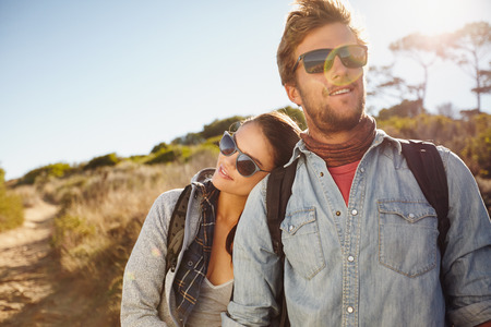 Portrait of young couple in love on hike. Young beautiful couple hikers in their twenties on hike. Young caucasian couple enjoying hiking in nature. Stock Photo