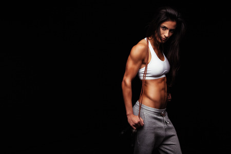 Confident young female athlete posing with jumping rope looking at camera. Muscular woman with skipping rope standing against black background