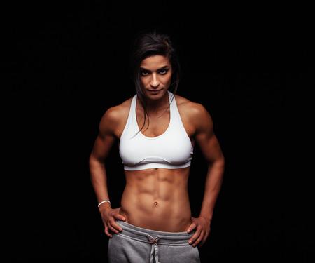 attitude: Foto de una mujer fuerte con el abdomen muscular en ropa deportiva. Modelo femenino de fitness posando sobre fondo negro. Foto de archivo