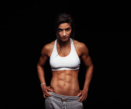 hands on stomach: Shot of a strong woman with muscular abdomen in sportswear. Fitness female model posing on black background.