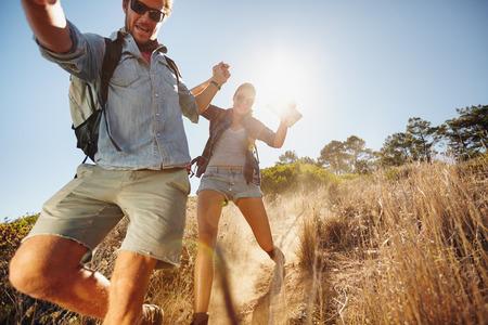 登山道を滑り降り、ハイキング旅行で楽しんで幸せな若いカップルの肖像画。夏休みで楽しんでいる白人のハイカーのカップル。