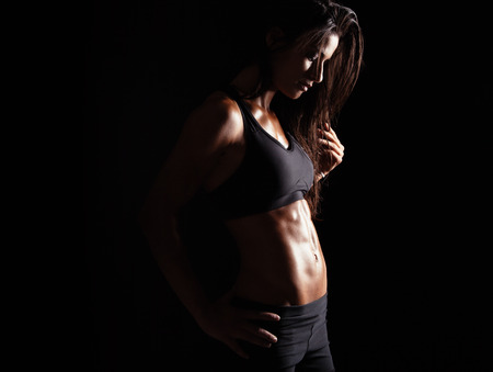 Image of female in sports clothing relaxing after workout on black background. Muscular female body with sweat.