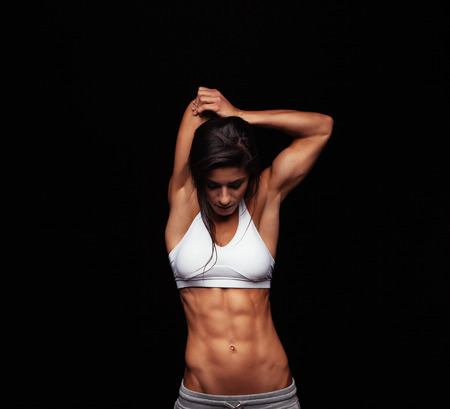 Studio shot of muscular young fitness model. Healthy young woman in sportswear exercising on black background. Фото со стока
