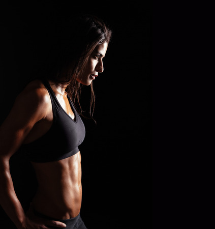 focus on: Image of fitness woman in sports clothing looking away on black background. Young female with perfect muscular body. Determination and confidence.